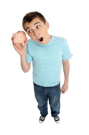 A pre teen boy shakes a money box piggy bank photo