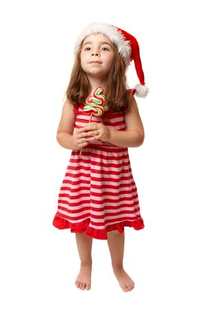 A small girl wearing a santa hat and holding Christmas candy. photo