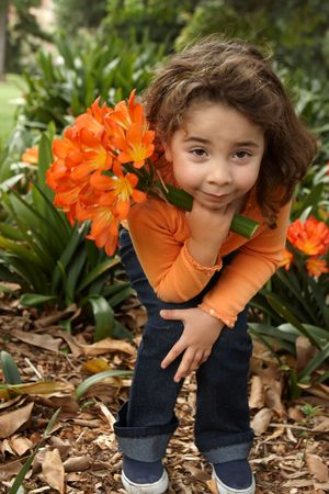 Little girl holding a bunch (umbels) of lilies  (clivia miniata).  She is wearing navy jeans and an orange twin set and  standing in the garden bed. photo