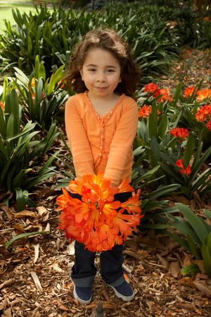Little girl with a bunch of clivia miniata (bush lilies) from the garden photo