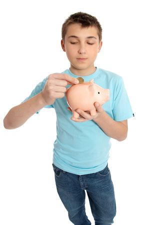 A child placing a coin into a pink pig money box. photo