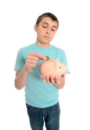 A boy puts spare change coins into a money box. photo