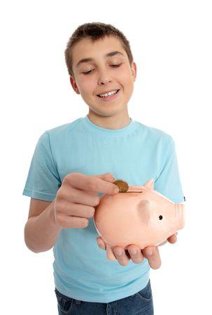Smiling boy dropping a gold coin into a money box. photo