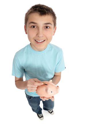 Happy pre teen boy putting coins into a money box photo