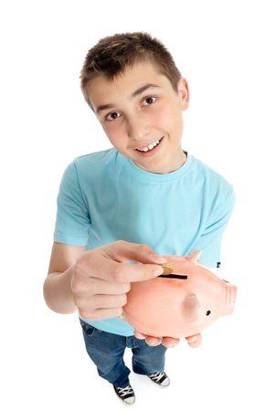 A boy holding a piggy bank money box drops a gold coin inside photo