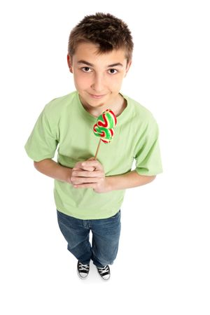 A boy wearing jeans and a t-shirt is holding a Christmas tree lollipop on a stick photo