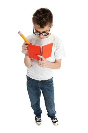 A geeky boy scribbles down notes in a notebook Stock Photo - 5799722
