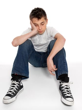 listless: A pre teen boy sitting on the floor with head in hand, bored, grief, troubled or destitute