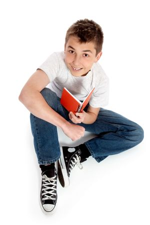 Pre teen boy sits casually on the floor with a book.  He is wearing jeans, t-shirt and sneakers and looking up at camera and smiling cheerfully.  Shadow under boy. photo