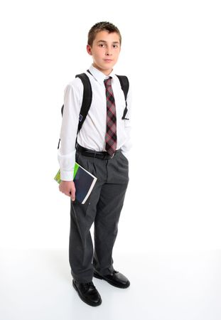 A high school student wearing a white shirt, tie and grey trousers.  He is carrying a backpack on his shoulders and some books in one hand.