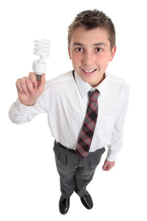 environmental issues: A pre teen high school student in uniform holds a light bulb - ideas, inspiration or environmental issues