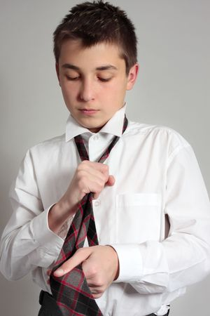 tween boy: A school student getting dressed in uniform for school Stock Photo