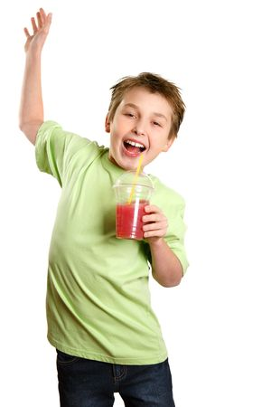sipping: A boy jumps in delight.   He is holding a healthy fruit juice and smiling with glee. Stock Photo