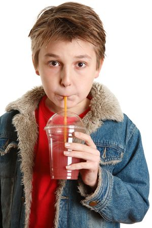 A young boy drinking fresh mixed berry health juice in a clear cup container with a yellow straw.  He is wearing a red t-shirt and a blue denim jacket. photo