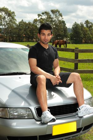 A casual dressed attractive man sitting on car bonnet of a silver sedan vehicle in the late afternoon. photo