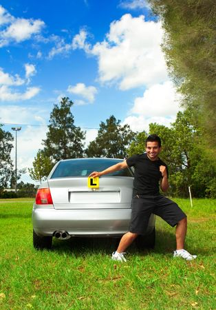 Excited male driver holding licence plates to rear of silver motor vehicle.  He is smiling and making a victory fist. Stock Photo - 6407681