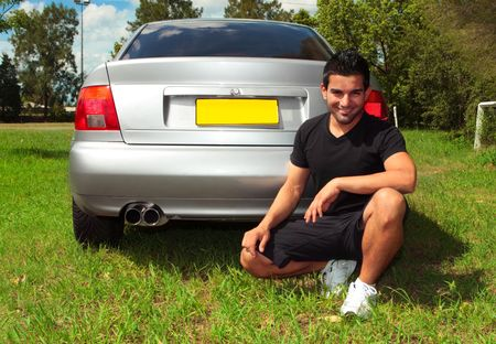 A smiling man beside rear of a a silver car vehicle Stock Photo - 6407680
