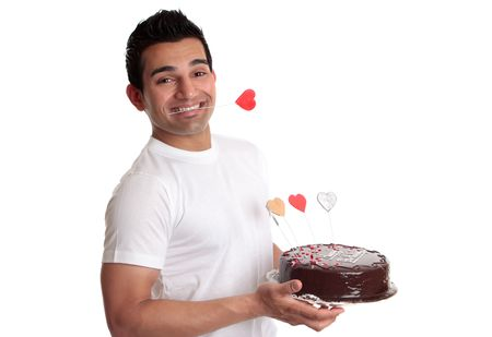 A man holds a chocolate mud cake decorated with love hearts.   He has a red love heart clenched between his teeth.  Suitable for birthday or special occasion. Stock Photo - 6422113