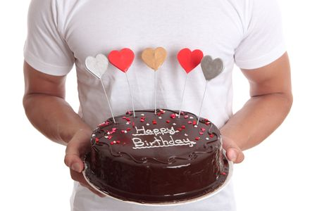 Man holding a chocolate birthday cake with lovehearts.  Closeup photo