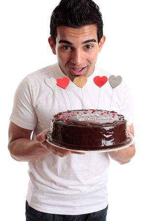 Cheeky male about to bite one of the hearts on a chocolate birthday cake photo