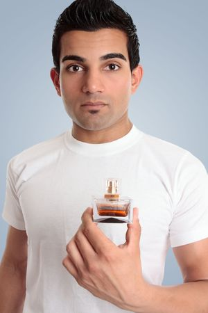 A man holds a bottle of spray cologne perfume in one hand.  He is dressed casually in a white t-shirt. Stock Photo - 6511151
