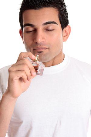 Un chico o un cliente sostiene una botella de Colonia de perfume para oler su perfume de fragancia. Foto de archivo