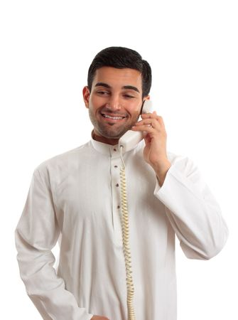 A middle eastern man in traditional clothing is talking on a telephone. photo