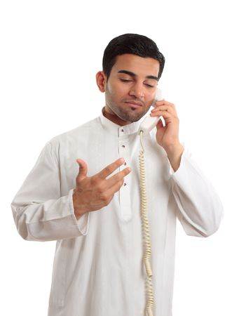 thobe: A middle eastern arab business man wearing an embroidered white kurta, thobe, robe, tunic, etc with ruby gemstone buttons, talks on a standard telephone