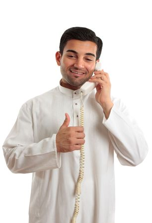 thoub: Happy ethnic mixed race businessman on telephone with thumbs up approval, success hand sign.   He is wearing a traditional robe, thobe, kurta with buttons of red burmese rubies set in silver.