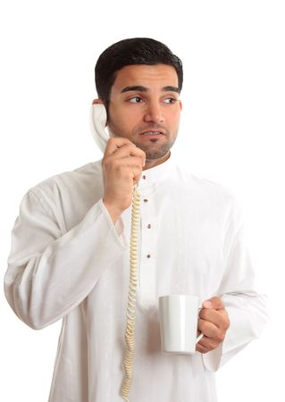 thoub: Unsure businessman from middle east, India or south east asia.  He is wearing a traditional robe, is on the telephone and  looks worried or anxious while looking sideways - white background