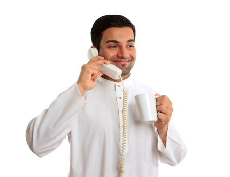 kameez: An arab business man dressed in traditional white  robe, eg kameez, thobe, kurta, etc.  He is holding a coffe whilst talking on a telephon and smiling.