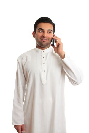 thoub: A happy ethnic arab middle eastern man talks happily on a mobile phone.  He is dressed in traditional white kurta, thobe, dishdasha fixed with silver buttons inlaid with burmese rubies.