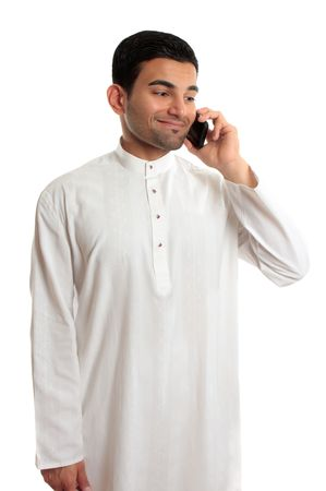 kurta: Ethnic mixed race middle eastern man in traditional dishdasha, kurta, thobe, robe, with silver buttons inlaid with rubies is chatting on a mobile phone, cellphone. Stock Photo
