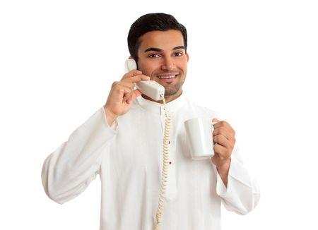 south east asian: Un amistoso sonriente �tnico �rabe empresario en una llamada telef�nica.  Est� celebrando una taza de caf� y lleva ropa tradicional de east asian Oriente o del Sur. Foto de archivo