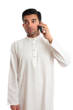 kurta: An ethnic businessman in a kurta, dishdasha, thobe, robe, traditional attire, is making a phone call using a mobile phone.  He is glancing sideways.