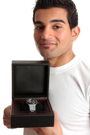 Closeup of a man holding a wristwatch sitting ina in a black box case. photo