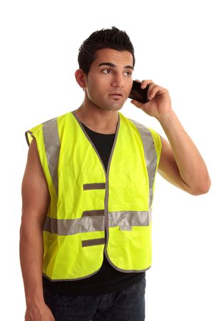 Construction worker in safety vest receives a call on a mobile phone. Stock Photo - 6803351