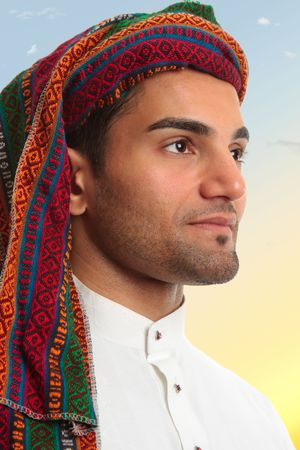 thoub: An arab middle eastern man looks out expectantly, earnestly.  He is wearing traditional clothing Stock Photo