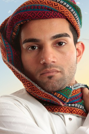 thoub: Arab man wearing a colourful wovan keffiyeh or turban style  head piece.  These headdresses serve a purpose of protecting nose and mouth from dust and sand storms as the fabric can be wrapped across the face when needed. Stock Photo