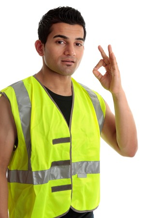Ethnic mixed race, blue collar man such as a builder, tradesman, labourer, handyman gestures a positive a-ok approval hand sign gesture.  White background. photo