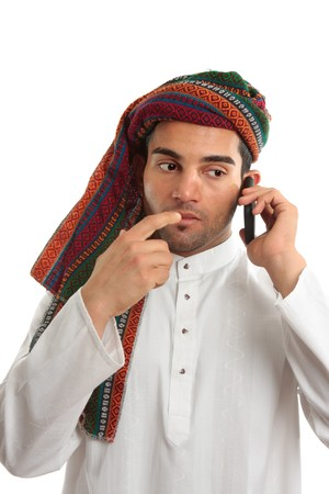 thoub: Pondering arab ethnic middle eastern businessman dressed in traditional clothing.   He is using a mobile cellphone. White background. Stock Photo