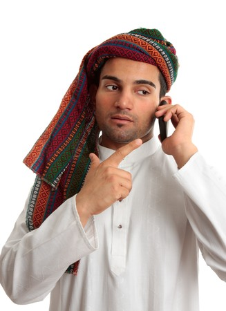 thoub: A middle eastern businessman talks on a mobile cell phone.  White Background.