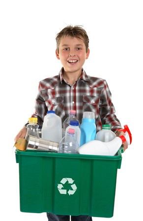 A happy smiling boy carrying a container bin of cans and bottles suitable for recycling.  White background.