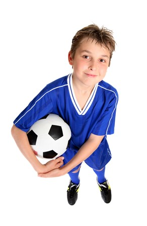 A smiling boy in soccer uniform ready for a game of soccer.  White background.