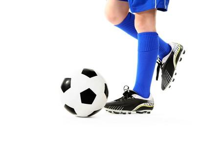 Boy kicking a soccer ball. White background.