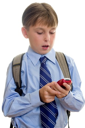 A schoolboy student using a mobile cell phone is sms or texting.  White background. Stock Photo - 7147984