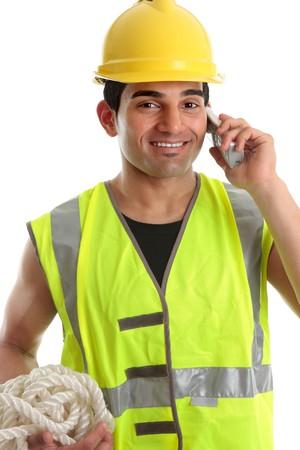 obrero: Happy sonriendo generador, ingeniero civil, trabajador de la construcci�n, trabajador utilizando un tel�fono. Lleva sombrero amarillo de disco duro y chaleco reflectante de alta visibilidad. Fondo blanco.