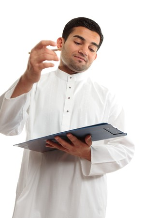 qameez: An ethnic middle eastern mixed race business man wearing a white traditional woven robe and holding a clipboard folder and pen.   Mans right hand shows motion.