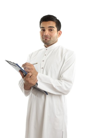 qameez: Traditional ethnic businessman facing slightly sideways.  He is wearing white woven robe with ruby buttons.  He is holding a clipboard folder and pen.  White background. Stock Photo