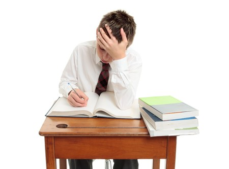 A high school student sitting at desk studying or learning.  White background.